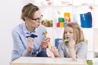 teacher using colorful toys during play therapy with child